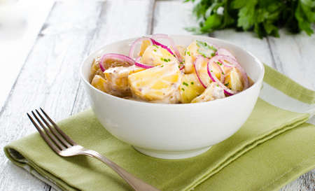 Fresh potato salad with mayonnaise dressing, onion and capers on white Stock Photo