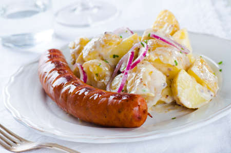 grilled sausage with classical potato salad with mayonnaise dressing on white
