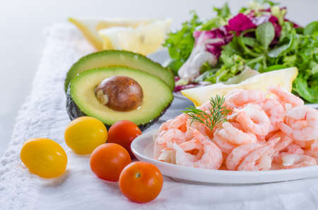 Shrimp salad ingredients - cooked, peeled shrimps, salad, tomatos, avocado