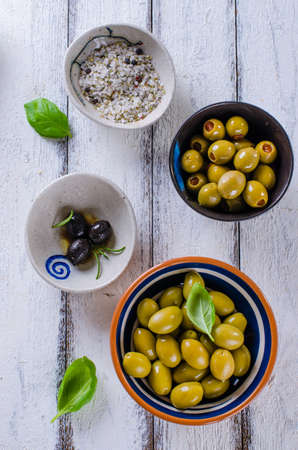 Assortment of olives with herb and sea salt on white wooden background