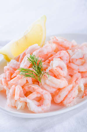 shrimps - cooked and peeled with lemon wedge on white