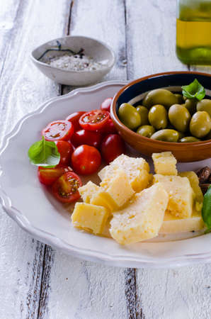Antipasti plate of parmesan, cherry tomatoes, olives and almonds