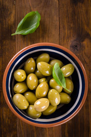 Green olives in a ceramic bowl on wooden background