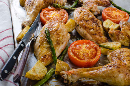 Roasted chicken legs with tomato and asparagus Stock Photo