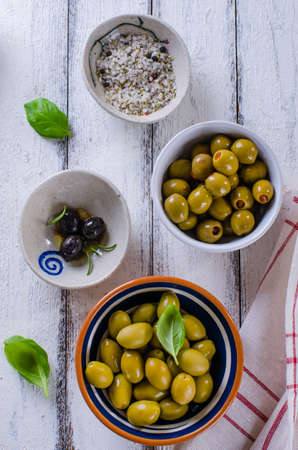 Black and green olives on a white wooden background
