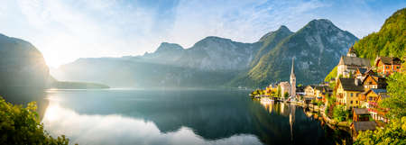 Panorama view of famous old town Hallstatt and alpine deep blue lake with tourist ship in scenic golden morning light on a beautiful sunny day at sunrise in summer, Salzkammergut, Austria