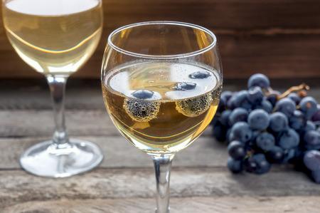 lambrusco: Sparkling wine lambrusco in glass. Ripe grape in wine glass with bubbles. Stock Photo