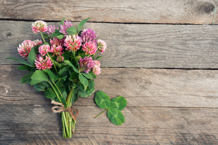 Clover bouquet with leaves on wooden background. Top view.