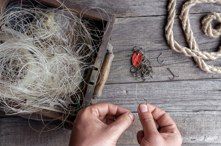 crotchet: Fisherman prepare to fishing. Tools and accessories on wooden table.