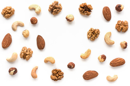 Isolated nuts pattern backdrop with copy space. Walnut, cashew, almond and hazelnut on white background.