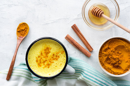 Turmeric latte, Cooking Golden Milk On Kitchen. Hot healthy drink. Top view. 스톡 콘텐츠