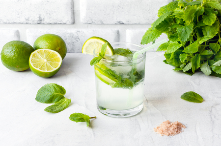 Mojito Cubano (caipirinha cocktail) with lime and mint on a concrete table. 스톡 콘텐츠