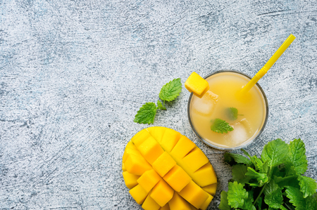 Healthy mango smoothie drink in a glass with mint on concrete table. Top view. Copy space. 写真素材