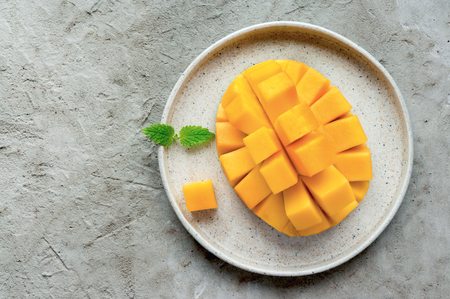 Healthy breakfast. Sliced mango fruit on plate. Top view. Concrete background with copy space.