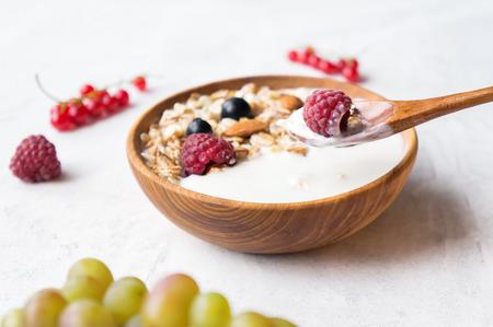 Healthy breakfast. Bowl of muesli with natural yogurt, almonds and fresh raspberries. Selective focus.