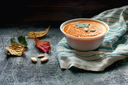 Healthy creamy pumpkin soup. Dry autumn leaves decoration. Selective focus. Stock fotó