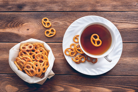 Cup of tea and sweet mini pretzels on the wooden background. Top view.