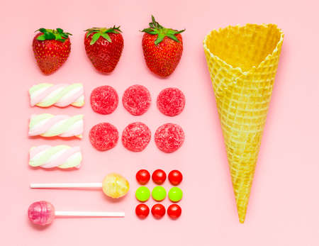 Creative photo of a waffle cone with fruits and sweets on pink background.