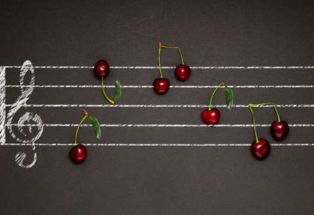 pentagrama musical: Creative concept photo of an illustrated musical staff with cherries as notes on black background.
