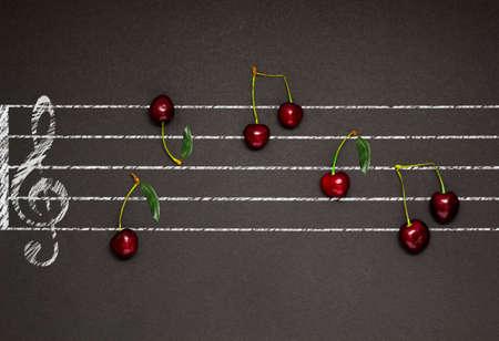 pentagrama musical: foto concepto creativo de un personal musical ilustrada con cerezas como notas sobre fondo negro.