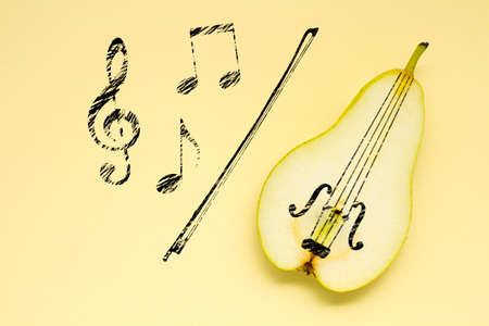 Creative concept photo of a pear as a violin with illustrated bow and notes on yellow background. Stock Photo