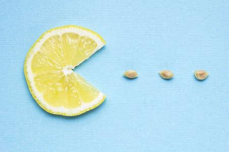 lemony: Creative concept photo of a lemon slice eating seeds on blue background.