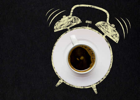 12 o clock: Creative concept photo of a coffee cup on a plate and illustrated alarm clock on black background.