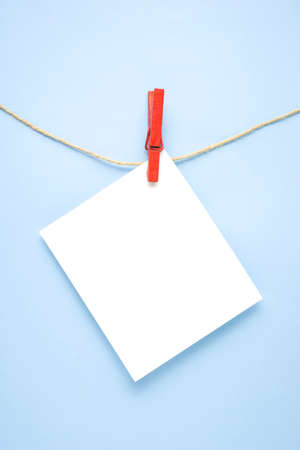 Creative concept photo of list with pin clothes peg on blue background. Banco de Imagens