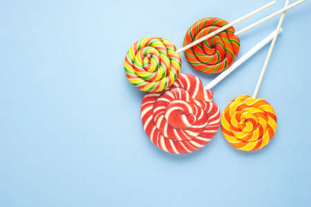 Creative concept photo of lolli pop candy on blue background.