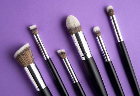 Creative concept beauty fashion photo of cosmetic product make up brushes kit on purple background. 写真素材