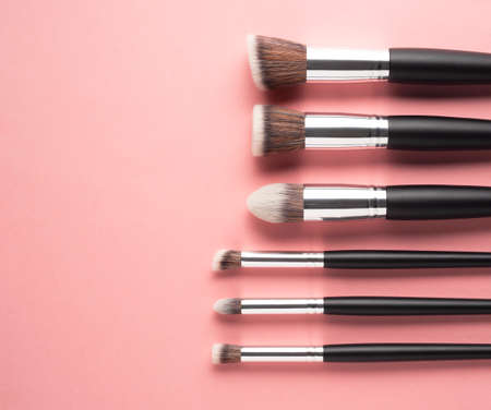 Creative concept beauty fashion photo of cosmetic product make up brushes kit on pink background.