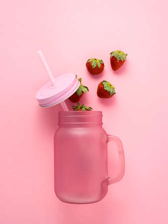 Creative food concept photo of cocktail glass with straw and strawberry milkshake on pink background. Imagens