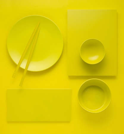 Creative concept health diet asian japanese food photo of painted plates dishes tableware with chopsticks on yellow background. Stockfoto