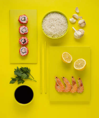 Creative concept health diet asian japanese food photo of painted plates dishes tableware with sushi roll and chopsticks on yellow background.