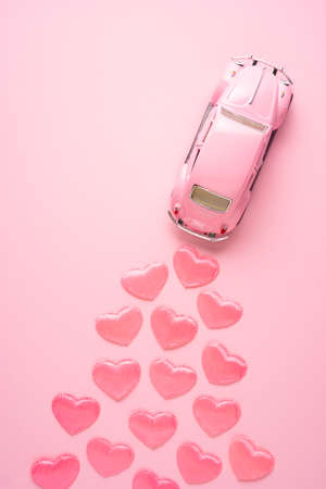 Creative concept holiday valentines day photo of car vehicle automobile toy driving with hearts on pink background. 版權商用圖片