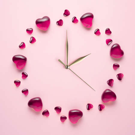 Creative concept holiday valentines day love photo of hearts in shape of time clock on pink background. Stock Photo