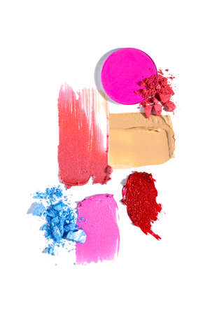 Creative concept fashion flatlay photo of cosmetics swatches beauty products lipstick eyeshadow cream foundation on white background.