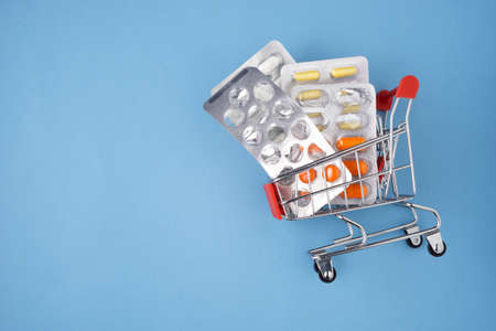 Creative healthcare and medicine concept photo of shopping cart with drugs and pills on blue background. Stock Photo