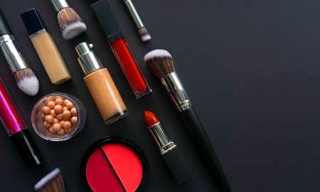 Creative concept beauty fashion photo of cosmetic products make up brushes kit lipstick foundation cream eyeshadows on black background.