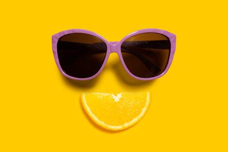 Creative food health diet concept photo of orange slice with sunglasses on orange background. Stock Photo