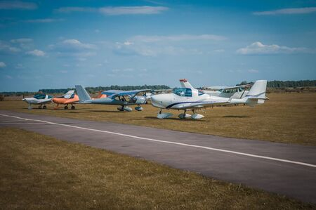 Several private small planes on aerodrome with bluse sky and green grass