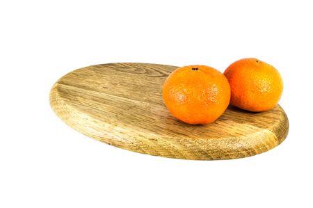 Orange mandarins or tangerines on cutting board isolated on white background. Closeup photos of fresh citrus fruit.