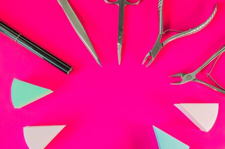 Manicure and pedicure tools on pink background. Nail file, scissors, tweezers pusher, nippers. Medical tools top view.