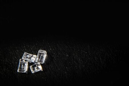 White sugar crystals on a black background in macro. Food photo with copy space  can be used like postcard
