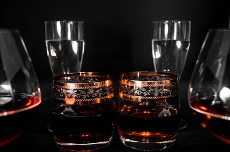 Glasses with different drinks. Brandy, whiskey, champagne or bourbon isolated on black background. Closeup photo of alcohol 版權商用圖片