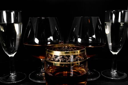 Glasses with different drinks. Brandy, whiskey, champagne or bourbon isolated on black background. Closeup photo of alcohol