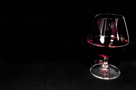 Glass of dark red for brandy,   whiskey or bourbon isolated on black background. Closeup photo of alcohol 版權商用圖片