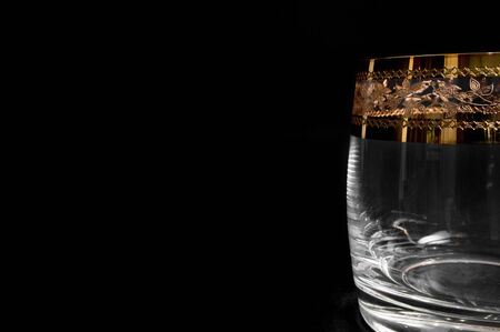 Empty glass for whiskey, brandy or bourbon isolated on black background. Closeup photo of  tumbler 版權商用圖片