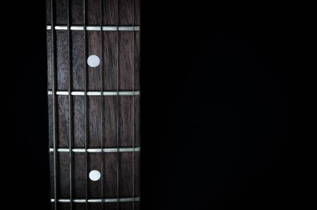 Fingerboard of red electric guitar closeup isolated on black background