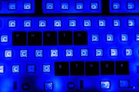 Abstract background of black computer keyboard without buttons with blue backlight. Word PHOTO STOCK from buttons on keyboard. 写真素材
